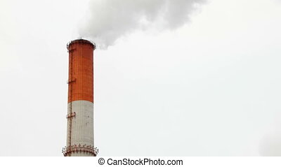 Boiler house chimney. Steam against the cloudy snowy sky. Industrial zone of the city.