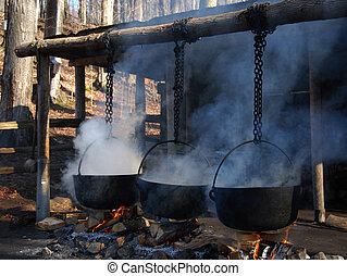 Traditional way of making maple syrup by boiling the sap in a cauldron- great halloween theme as well