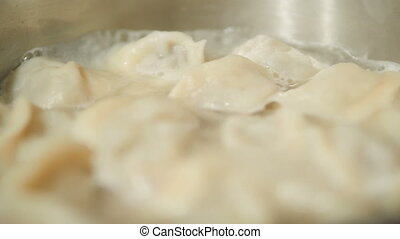 Boiling dumplings. Hot water with traditional dish of...
