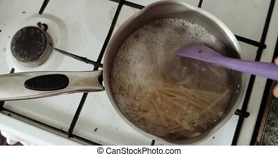 saucepan of boiling pasta on a gas burner in kitchen -...