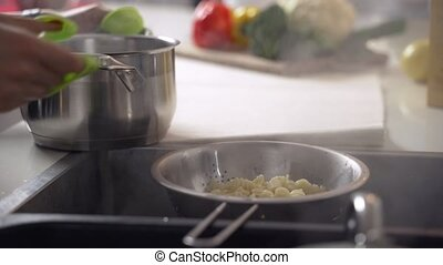 Boiling pasta. Draining macaroni water through a colander in...