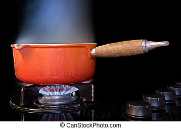 Boiling pot of water - A boiling pot of water on a black ...