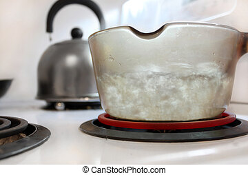 Boiling water in glass pot on stove with kettle in the background (shallow depth of field)
