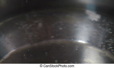 Boiling water in a kitchen pot as a symbol of cooking or...