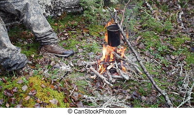 Boiling water in pots above the fire in outdoor