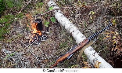 Boiling water in pots above the fire in outdoor. Hunter shotgun
