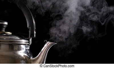 Boiling water in teapot with steam, slow motion