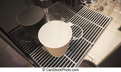 Boiling water pours into a disposable cup out of a coffee...