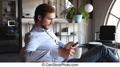 boire, jeune, homme affaires, utilisation, thé, bureau, smartphone