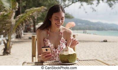 boire, sourire, utilisation, plage, smartphone, femme, eau noix coco