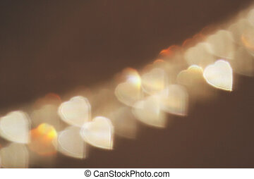 Bokeh blurred heart shape lights on the brown background