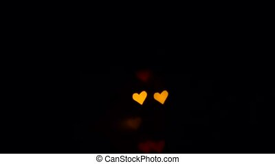 Bokeh color heart lights flashing in dark. St. Valentine day background
