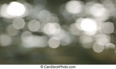 Bokeh of sun glares reflected from water