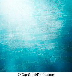 Bokeh summer sea background. Small waves on water surface in...