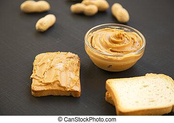 bol, beurre arachide, pains grillés, unshelled, cacahuètes, sur, arrière-plan noir, côté, vue., close-up.