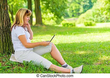 boldog, megfontolt woman, a parkban, noha, egy, laptop
