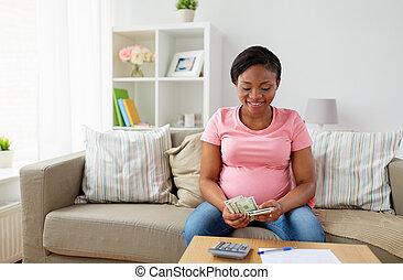 boldog, terhes nő, számolás, pénz, otthon