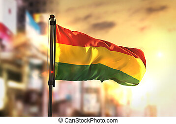 Bolivia Flag Against City Blurred Background At Sunrise Backlight