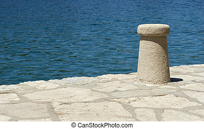 Bollard on the Pier - Mooring post on the pier by blue sea.