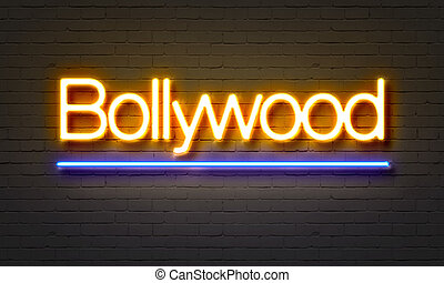 Bollywood neon sign on brick wall background.