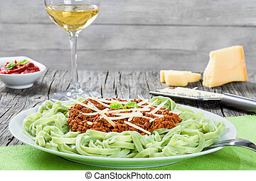 Bolognese ragout with green  pasta tagliatelle, top view