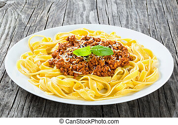 Bolognese ragout with italian pasta on a white plate, close-up