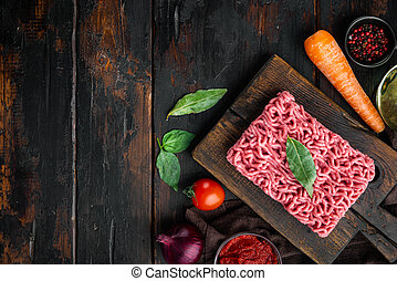 Bolognese sauce ingredients, minced meat tomatoe and herbs, on wooden cutting board, on old dark wooden table background, top view, flat lay, with copy space for text