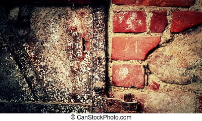 Bolts and nuts on the door connected to the brick wall