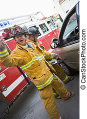 bombero, hacer señas, para, reserva, con, otro, bombero, utilizar, el, mandíbulas, de, vida, en, un, puerta de automóvil, (blur)