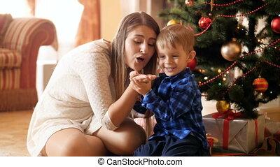 bon, amusement, avoir, confetti, arbre, vidéo, étincelant, room., peu, celebrations., heureux, fils, sous, temps noël, séance, main, vivant, mouvement, elle, famille, hiver, lent, souffler, fetes, sourire, mère, quoique