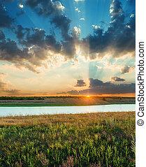 bon, coucher soleil, dans, bas nuages, sur, rivière, et, pré vert