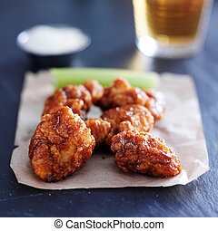 boneless barbecue chicken wings with beer on slate surface