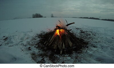 Bonfire burning in the darkening snowy field, 4K - Bonfire...