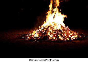 close up of bonfire and flames on a black background