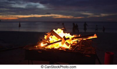 Bonfire in a grill on a beautiful beach during sunset.