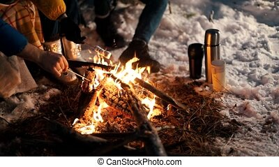 Bonfire in the winter forest. Night time. Frying marshmallow. Thermocouples stand in the snow
