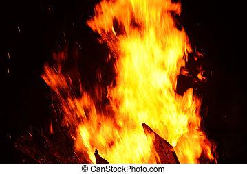 bonfire night campfire wood burning flame on dark black