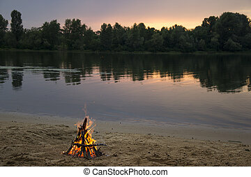 Bonfire on the bank of the river at sunset