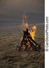 Bonfire on the sandy beach after sunset