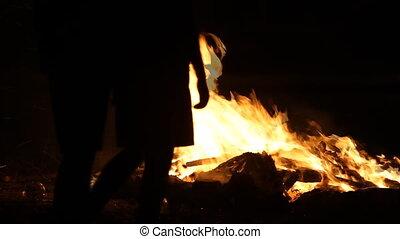 People silhouette around bonfire in the dark night