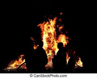Silhouettes of people in front of bonfire