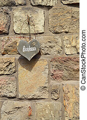 Bonheur - Stone wall with wooden Heart shape with text ...
