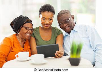 bonito, adulto jovem, africano, menina, com, sênior, pais, usando, tabuleta, computador