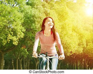 bonito, asiático, mulher jovem, bicicleta equitação, parque