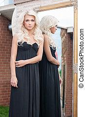 bonito, blonde., atraente, jovem, cabelo loiro, mulher, em, vestido preto, ficar, perto, a, espelho, e, olhando câmera