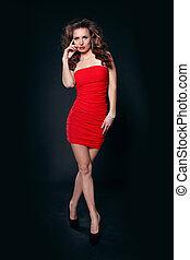 bonito, cabelo, mulher, cacheados, sobre, escuro, posar, fundo, excitado, vestido, vermelho