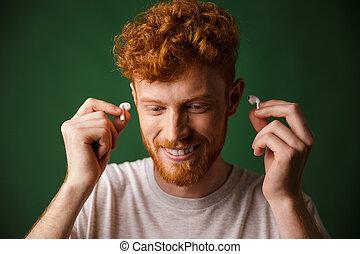 bonito, cacheados, ruivo, homem, em, t-shirt branco, inserção, fones ouvido, em, seu, orelhas