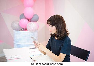 bonito, cor-de-rosa, mulher, escritório, negócio, sentando, notas, telefone pilha, enquanto, local trabalho, segurando, retrato, fazer, smartphone.
