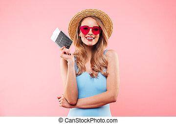 bonito, desgastar, mulher, óculos de sol, fundo, palha, sobre, isolado, swimsuit, um-pedaço, bilhetes, enquanto, cor-de-rosa, passaporte, segurando, sorrindo, chapéu