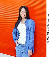 bonito, desgastar, mulher, sobre, calças brim azuis, jovem, fundo, sorrindo, roupas vermelhas